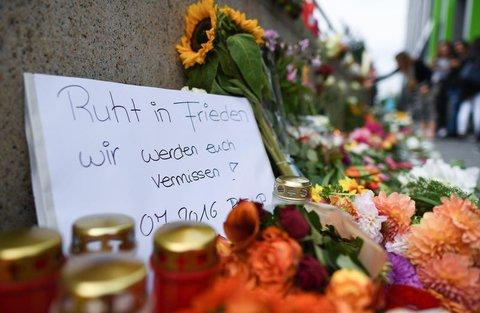 Blumen und Kerzen in der Nähe des Olympia-Einkaufszentrums, auf einem Zettel steht