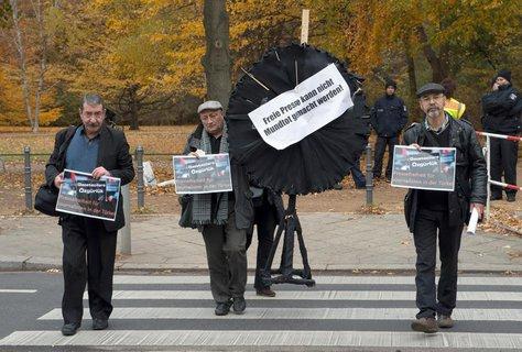 Mitglieder des Bundes türkischer Journalisten in Europa gehen am Freitag in Berlin mit Plakaten und einem schwarzen Kranz zur türkischen Botschaft. Nach der Verhaftung zahlreicher Journalisten in der Türkei, hatte der Bund türkischer Journalisten in Europa zu der Protestaktion vor dem Botschaftsgebäude aufgerufen.