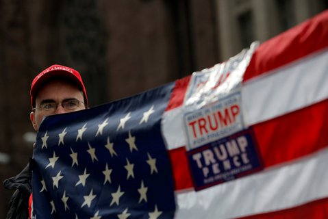 A man holds a flag during a rally in support of U.S. President Donald Trump at Trump Tower in Manhattan, New York, U.S. X02844 / REUTERS