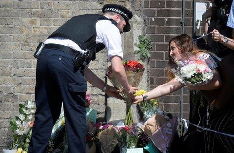 Ein Polizist hilft einer Frau in der Nähe des Anschlagsortes, Blumen abzulegen. Foto: REUTERS/Hannah McKay