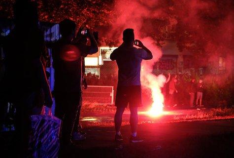 Schaulustige filmen im Schanzenviertel die Auseinandersetzungen mit der Polizei. Foto: Marcus Brandt/dpa