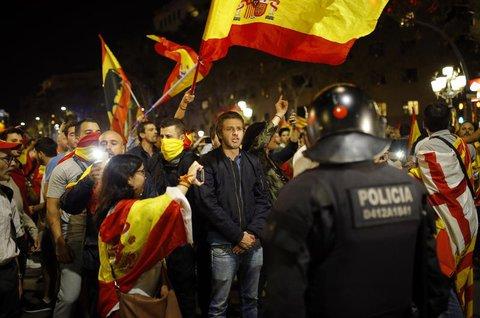 Unabhängigkeitsgegner rufen Slogans und schwenken spanische Flaggen, während sie nach der einseitigen Unabhängigkeitserklärung der katalanischen Regionalregierung  durch Barcelona marschieren. Foto: dpa