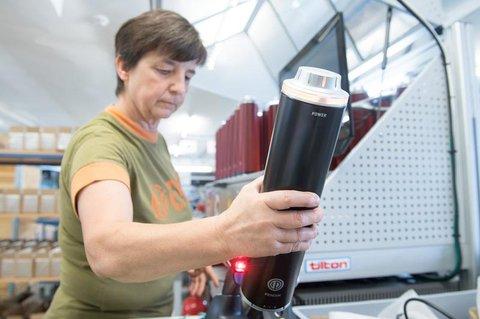 Produktionsarbeiterin Silke Streicher scannt an einem Prüfstand einen Fahrrad-Akku.