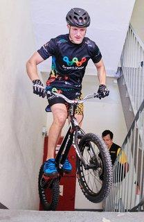 Der polnische Trial Biker Krystian Herba springt mit seinem Rad im Treppenhaus des Park Inn Hotels eine Treppe hinauf.