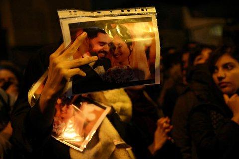 Eine Frau hält bei einer Demonstration ein Bild eines frisch verheirateten Paares in die Luft. Der Mann und die Frau waren beim Abschuss der ukrainischen Maschine ums Leben gekommen.