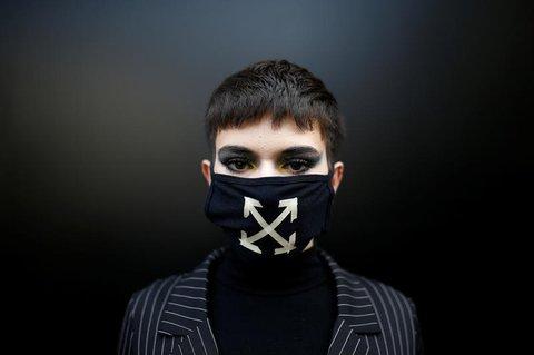 Ein Besucher der Modeschau mit Maske.