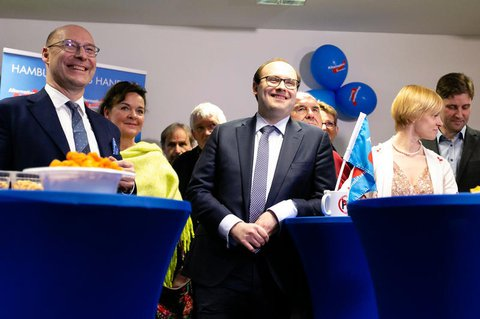 Alexander Wolf (l) und Krzysztof Walczak (M), beide stellvertretende Sprecher  der AfD Hamburg, stehen an einem Tisch während der  Wahlparty der AfD.