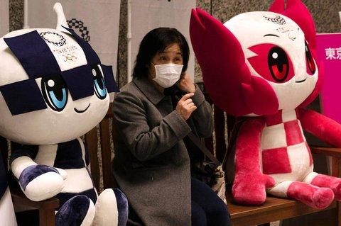 Eine Frau mit Mundschutz sitzt zwischen den Maskottchen der Olympischen und  Paralympischen Spiele 2020 in Tokio.