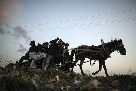 Türkei, Edirne: Migranten sind in der Nähe der türkisch-griechischen Grenze auf  einem Karren unterwegs, der von einem Pferd gezogen wird.