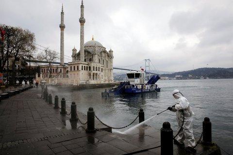 Am Montag versprüht ein Arbeit Desinfektionsmittel vor der Ortakoy-Moschee in Istanbul.
