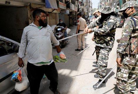 Polizisten in Neu-Delhi bestrafen einen Mann, der sich nicht an die Ausgangssperre hält