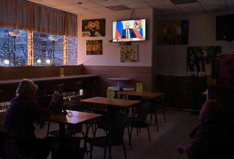 Eine Frau lauscht der Fernsehsprache Wladimir Putins in einem Café. Das ist ab Samstag nicht mehr möglich.