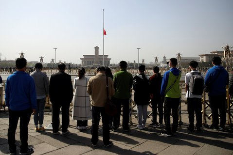 Menschen stehen am Tiananmen  Platz in Peking und gedenken der Toten der Coronavirus-Epidemie.