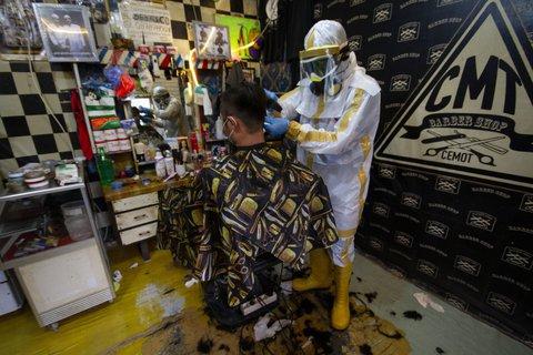 Gut eingepackt: Friseur Herman Maulana aus dem indonesischen Bogor bei der Arbeit.
