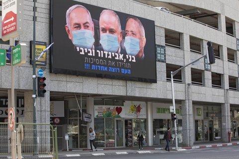 So wird es gemacht: Eine elektronische Anzeigetafel an einem Gebäude zeigt den israelischen Ministerpräsidenten Benjamin  Netanjahu (von links nach rechts) und die beiden Parteivorsitzenden Avigdor Lieberman und Benny Gantz mit Mundschutz.