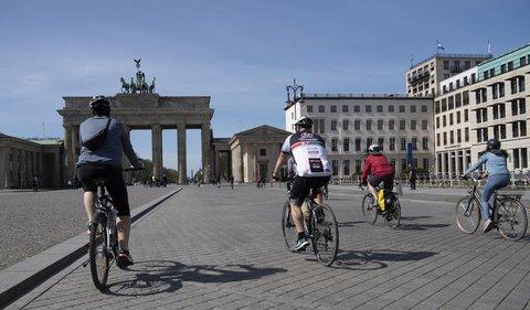 Fahrradfahrer auf dem fast menschenleeren Pariser Platz am Brandenburger Tor.
