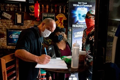 Ein Mitarbeiter nimmt die Kundendaten von zwei G?sten in einer Bar in New Orleans auf.