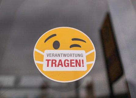 Dresden: Ein Smiley-Aufkleber mit einem Mundschutz und der Aufschrift