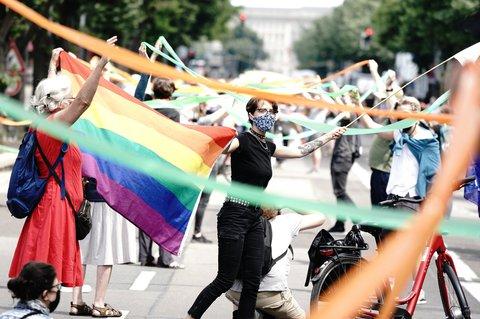 Mit Mundschutz und Regenbogenfahne halten Demo-Teilnehmende grüne und orangefarbene Bänder.