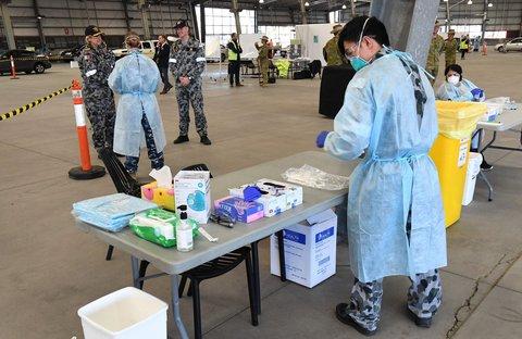 Ein medizinischer Mitarbeiter steht an einer Corona-Teststation in Melbourne.