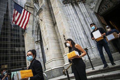 Trauernde tragen Kisten mit der Asche von Angehörigen, die an Covid-19 gestorben sind, aus der St. Patrick's Kathedrale in New York