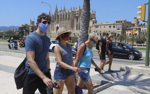 Junge Leute gehen mit Masken durch Palma de Mallorca.