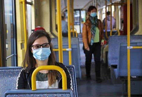 Frau mit Maske sitzt im Bus in Köln. NRW ahndet Verstöße gegen die Maskenpflicht mit 150 Euro Bußgeld.