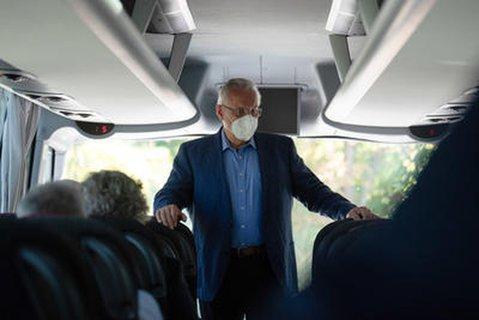 Bayern Innenminister Joachim Herrmann in einem Reisebus mit Mund-Nasenschutz.
