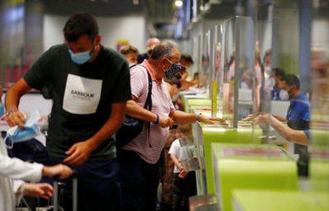 Touristen mit Mund-Nasenschutz am Flughafen der kanarischen Insel Gran Canaria