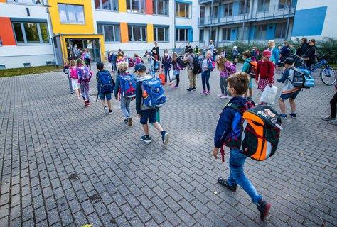Kinder gehen am Montag in eine Schule in Schwerin.
