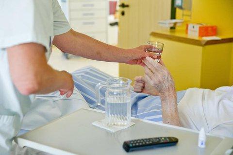Eine Pflegerin versorgt eine Patientin.
