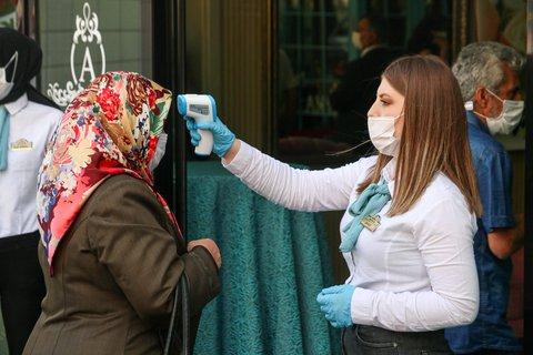 Eine Mitarbeiter des Veranstalters prüft die Temperatur eines Hochzeitsgastes in der Türkei.