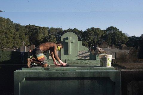 Ein Mann putzt einen Grabstein auf einem Friedhof in Rio de Janeiro.