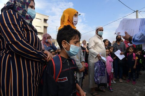 Schüler stehen gemeinsam mit ihren Eltern vor einer Grundschule in Tunis.