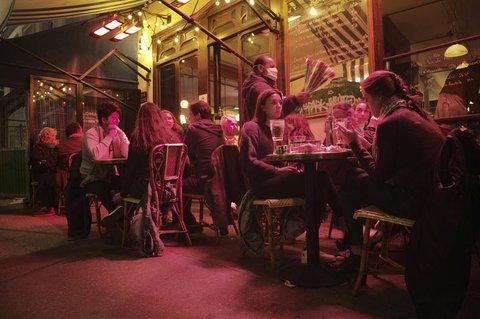 Gäste sitzen auf einer Caféterrasse in Paris.
