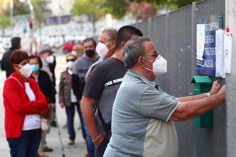 Hohe Zahl an Corona-Fällen: Menschen in Madrid stehen an, um sich auf das Coronavirus testen zu lassen.