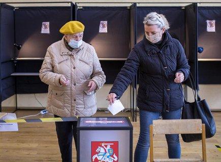 Zwei Wählerinnen in Vilnius tragen bei der Stimmabgabe für die zweite Runde der Parlamentswahl Mund-Nasen-Bedeckungen.