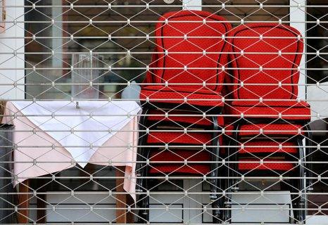 Hinter einem Gitter an einem geschlossenen Restaurant in Köln stehen Stühle.