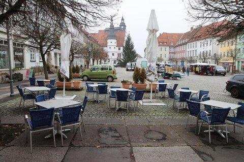 Leere Tische und Stühle stehen vor Cafes am Marktplatz von Hildburghausen.