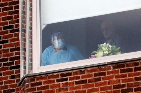 Eine Krankenschwester und ein Patient gucken aus demMontefiore New Rochelle Krankenhaus in New Rochelle, New York.