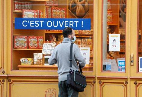 Ein Mann steht vor einem Geschäft in Paris.