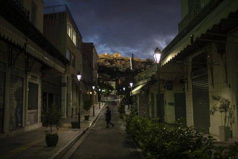 Eine Frau geht über eine verlassene Straße im Athener Stadtteil Plaka.