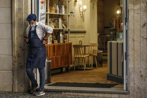 Ein Kellner mit Mund-Nasen-Schutz steht vor dem Eingang zu einem Café in Rom.
