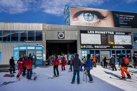 Wintersportler stehen auf einer Piste im Walliser Skigebiet vor einer Gondel Schlange.