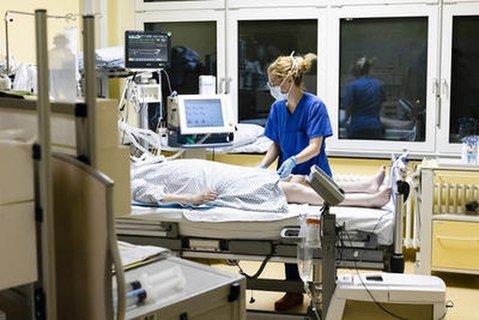 Eine Krankenschwester auf der Intensivstationam Universitätsklinikum Schleswig-Holstein steht am Bett einer Patientin.