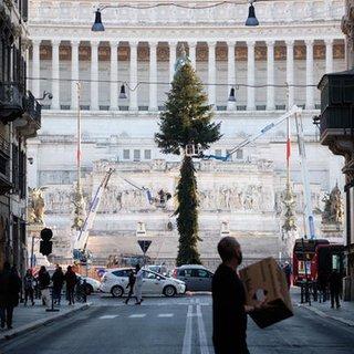Arbeiter stellen einen Weihnachtsbaum auf der zentralen Piazza Venezia in Rom auf.