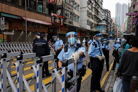 Polizisten in Schutzausrüstung stehen in dem Stadtteil hinter Absperrungen.