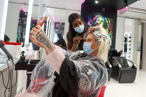 Als erster Kundin des Friseurladens Magali Coiffeur werden Arielle Rippegather nach der Wiedereröffnung die Haare geschnitten und gefärbt. Nach wochenlanger Zwangspause wegen der Corona-Pandemie sind bereits in der Nacht die ersten Friseure wieder ihrer Arbeit nachgegangen.