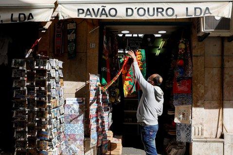 Ein Mann öffnet am Mittwoch seinen Laden in Lissabon wieder.