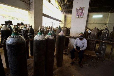 Ein Mann wartet, um eine Sauerstoffflasche zu befüllen.